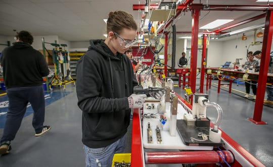 Derek Crawford works in a laboratory at Doss High School that simulates a manufacturing environment.  Academies of Louisville is part of JCPS' push to provide students with career options that include a chance to earn industry certifications. November 18, 2019