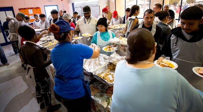 Mercedez Marquez, student with Goodwill Metro youth program, and Lance Meeks, program manager Goodwill Metro/REC youth program, volunteer to help serve Thanksgiving plates to the Homeless in Tucson, Ariz. at Armory Park, 220 S. 5th Ave., on November 22nd, 2019. Meeks manages the Goodwill Metro Youth Program, which started 5 years ago, to help youth and young adults between the ages of 16-24 with employment and education.  Goodwill Metro also offers participation in community events and give back to the community, said Meeks.