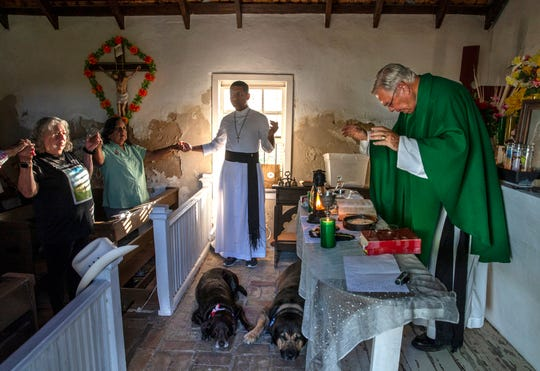 Father Roy Snipes says mass at La Lomita Chapel while his dogs, Charlotte, left and Bandito, right, lay on the brick floor. The chapel is at the center of a religious freedom lawsuit against the Federal government. The proposed border wall will cut off access to the site on the Rio Grande River. Sept. 17, 2019