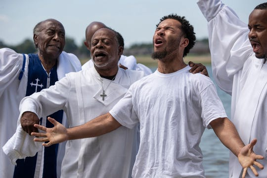 Darius Todd, 19, is baptized in the Ohio River by Rev. Charles Elliott Jr., on left, and other ministers from King Solomon Missionary Baptist Church. Aug. 4, 2019.