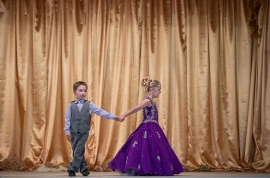 Ruby Craig, 5, leads Seth Zega, 5, from the stage after being named Little Miss and Mr. Oldham County and the Oldham County Fair. July 30, 2019.