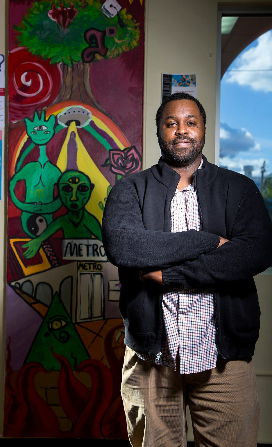 Lance Meeks, program manager Goodwill Metro/REC youth program, poses in front of a painting created by students at the reengagement center in Tucson, Ariz. on November 22nd, 2019.