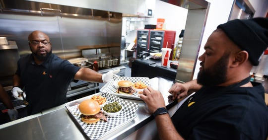 Gabe Jones, right, of Smoke 'N Pig BBQ, runs a tray of food prepared by Walter Pops, Thursday, Dec. 5, 2019, in their new brick and mortar restaurant in Delta Township.