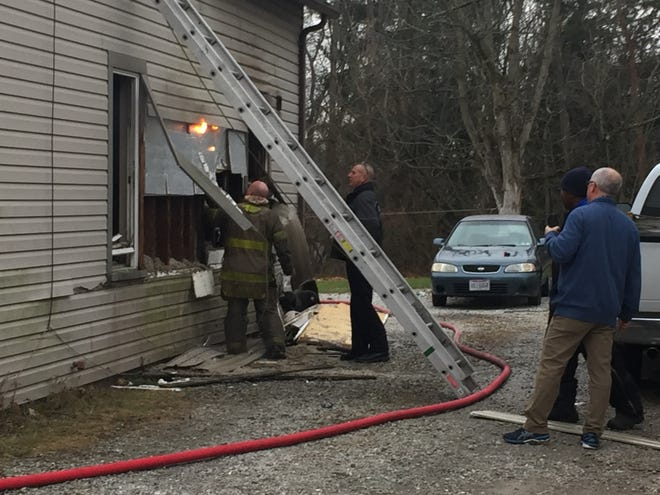 Flames reignited Friday morning at a house fire at 701 Springmill St.