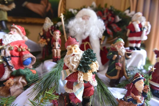 A large collection of Santa Claus statues decorates a table outside the kitchen at Kingwood Hall.