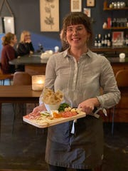"""Knifebird bartender Madeleine Holdford brings a """"house board"""" of cheeses and charcuterie to a table."""