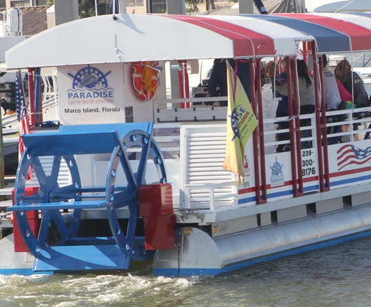 A big blue paddlewheel aft turns the cyclists' efforts into boat propulsion.