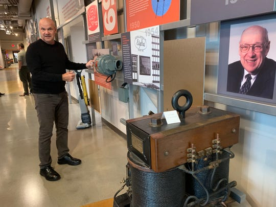 Chief marketing officer Russ Minick starts at the beginning of Generac's wall of history inside the firm's global headquarters. Generac, founded by Robert Kern (pictured on wall), celebrated its 60th anniversary in 2019.