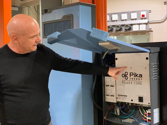 Russ Minick, chief marketing officer for Generac Power Systems, shows a key component in the firm's new clean-energy initiative. This power core was by Pika, a company acquired in spring 2019 that produced some cutting-edge technology in the creation of batteries useful for solar power storage.