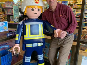 Todd Merryfield stands next to a large playmbobil figure, which can be found at one of his Learning Shop stores. Merryfield and his brother announced they are closing the stores at the end of 2019.