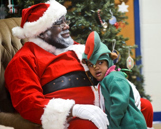 Santa (Robert Boyd) and his helper, Ra'Quell Boyd, 3, share a moment together between taking photos with families on Dec. 19, 2015 at Mt. Calvary Church. District Seven of the Milwaukee Police Department held a Christmas celebration for the community.