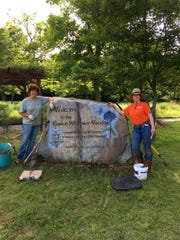 Joanne Rines and Paula Caprio, both of Marshall, pause near the Gaston Wildflower Meadow sign in Bull Shoals-White River State Park.