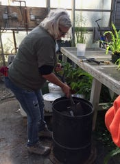 Jessi Dutton of Mountain Home mixes soil nutrients into potting medium for transplanting seedlings and rooted cuttings at Ozark Folk Center State Park's greenhouse.