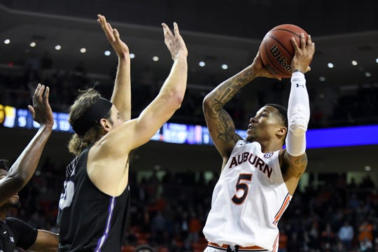 Auburn guard J'Von McCormick (5) shoots over Furman forward Clay Mounce (45) during the second half of an NCAA college basketball game Thursday, Dec. 5, 2019, in Auburn, Ala. (AP Photo/Julie Bennett)
