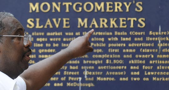 A man points at the marker in Court Square where slaves were auctioned in Montgomery.