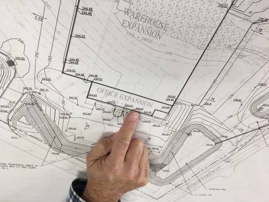 Group Vice President of Operations Bill Yeomans points to an expansion plan at Hager Companies in Montgomery.