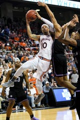 Auburn guard Samir Doughty (10) passes the ball around Furman guard Mike Bothwell (3) during overtime of an NCAA college basketball game Thursday, Dec. 5, 2019, in Auburn, Ala. (AP Photo/Julie Bennett)