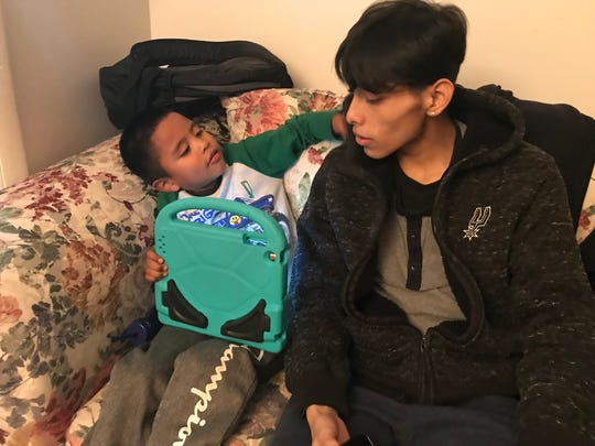 Josue Nandho, spends time with his little brother Jesus, playing a digital game.