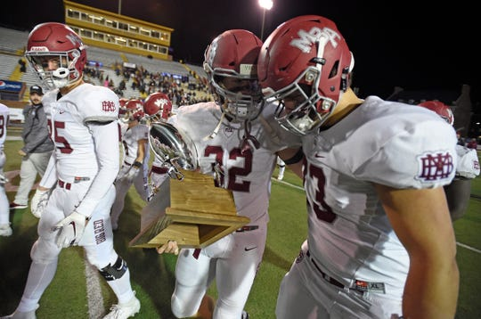 MBA's Hedges Hayworth (32) and Gaits Buntin (73)  carry the runner-up trophy off the field after losing to McCallie in the Division II-AAA championship at Tucker Stadium in Cookeville, Tenn., Thursday, Dec. 5, 2019.
