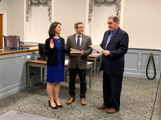 Beth Fischer is sworn in as Wyckoff Committee member next to husband Seth as Township Administrator Robert Shannon issue the oath of office.