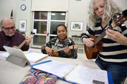 (From right)  Sue Zitelli, Joffin-Mari Motyka and Bob Kaminski  play ukuleles on Thursday, December 5, 2019. They are part of a ukulele group that gathers every Thursday.