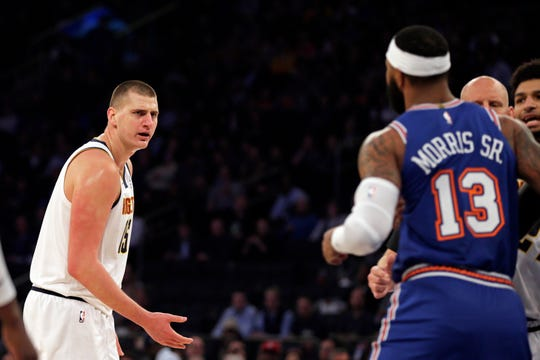 New York Knicks forward Marcus Morris Sr. (13) and Denver Nuggets center Nikola Jokic (15) exchange words during the first half at Madison Square Garden.