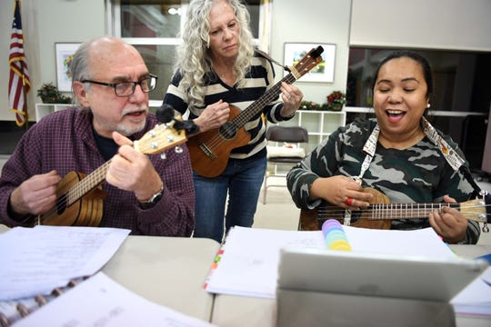 (From right) Joffin-Mari Motyka sings as she plays ukuleles with Sue Zitelli and Bob Kaminski on Thursday, December 5, 2019. They are part of a ukulele group that gathers every Thursday.