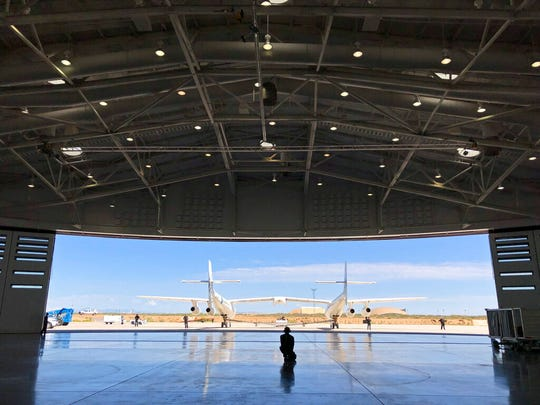 """In this Aug. 15, 2019 file photo, Virgin Galactic ground crew guide the company's carrier plane into the hangar at Spaceport America following a test flight over the desert near Upham, New Mexico. Virgin Galactic is on the verge of making more history in 2020 following an """"incredible"""" year of progress, the chief executive of billionaire Richard Branson's space tourism venture said Thursday."""