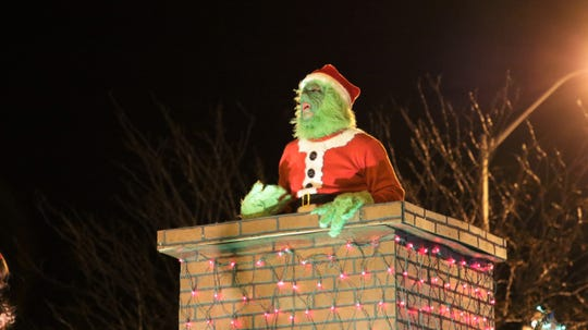 Dr. Seuss' The Grinch singing out of a chimney at Farmington's annual Christmas Parade in Farmington on Dec. 5, 2019.