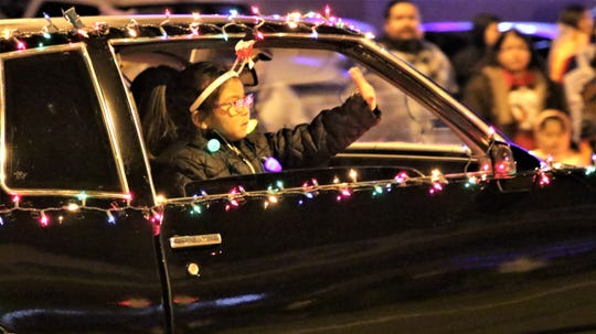 A child waves out of the car of a member of the Northern New Mexico Street Rodders at Farmington's annual Christmas Parade in Farmington on Dec. 5, 2019.