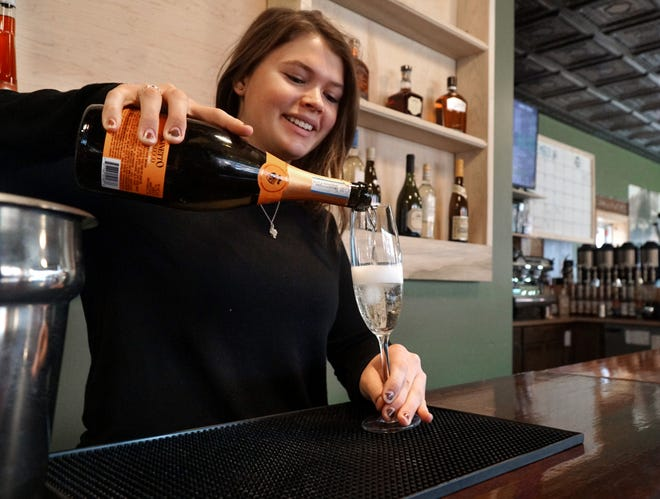 Corner Caffé' employee Ashley McGuire pours a little bubbly on Dec. 6, 2019 at the shop's new wine bar area. The coffee shop and restaurant will now be able to serve wine and spirits through late night at its downtown location.