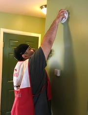 A volunteer reaches up high to install a smoke detector.