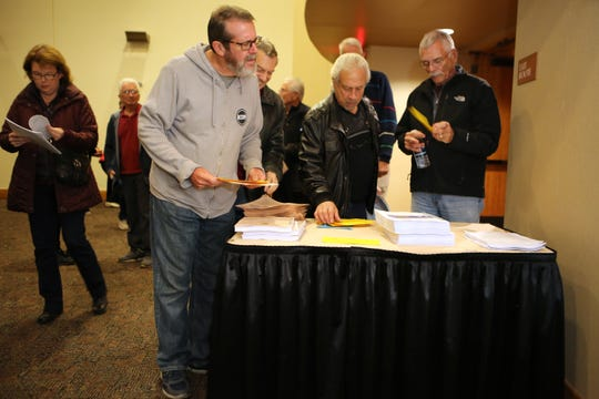 Residents pick up yellow cards to fill out so they may speak at the special City Council meeting regarding the arena at the Palm Springs Convention Center in Palm Springs, Calif., on December 5, 2019.