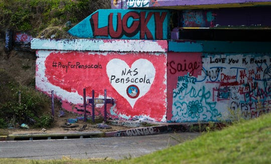 Pensacola resident Bradley Deal painted the Graffiti Bridge on Friday, Dec. 6, 2019, in honor of the victims in Friday's shooting at NAS Pensacola.