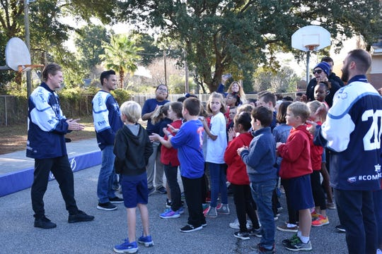Ice Flyers players Tyler Andrews, Joe Drapluk and Eddie Matsushima talking with kids Thursday at Cordova Park Elementary School.