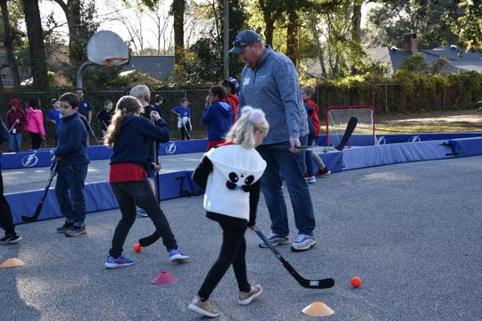 Ice Flyers owner Greg Harris working with two young girls during Thursday's visit with Tampa Bay Lightning Build The Thunder program at Cordova Park Elementary School.