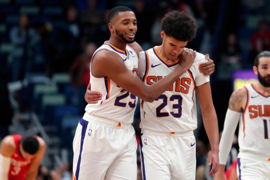 Phoenix Suns forward Mikal Bridges (25) embraces forward Cameron Johnson (23) during overtime of the team's NBA basketball game against the New Orleans Pelicans in New Orleans, Thursday, Dec. 5, 2019. The Suns won in overtime, 139-132. (AP Photo/Gerald Herbert)