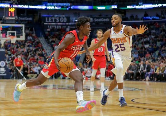 Pelicans guard Jrue Holiday drives past Suns forward Mikal Bridges during a game Dec. 5.
