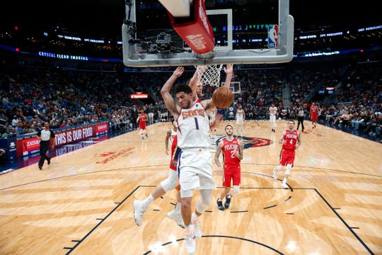 Phoenix Suns guard Devin Booker (1) slam dunks in front of New Orleans Pelicans forward Nicolo Melli in the first half of an NBA basketball game in New Orleans, Thursday, Dec. 5, 2019. (AP Photo/Gerald Herbert)