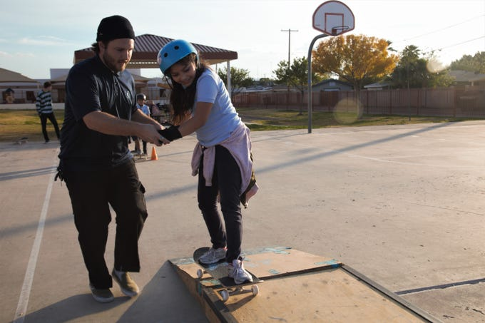 "Program lead Brian Masterson helps Diana Flores, 9, practice skating on a ramp during a Skate After School session at Gateway School on Dec. 5, 2019. ""This is my first time ever getting a brand-new skateboard,"" Diana said of the donated board she received that day."