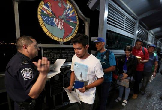 Inmigrantes caminan frente a autoridades de inmigración.