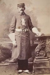 A cabinet photo of a member of the Vigilant Hook & ladder Company No. 1 in a parade uniform during the 1880's.