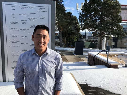 Lawrence Tam, a three-time national boxing champion at Nevada, stands in Jensen Plaza outside Mackay Stadium. Tam's name is on the sign behind him.
