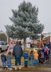 Yerington Elementary School students and teachers watch city employees hang their hand-made ornaments on a tree outside City Hall.