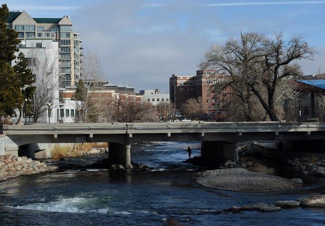 A person fishes under the Arlington Bridge near downtown Reno on Dec. 6, 2019.