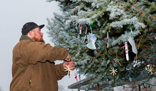 Yerington public works employee Monte Stanton prepares to hang a handmade ornament on a tree outside City Hall. The ornaments were made by Yerington Elementary School students.