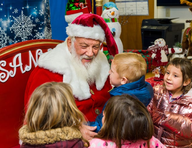 Students from Yerington Elementary School try to get a private word with Santa during his visit at Yerington City Hall.