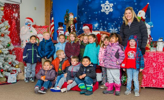 Students from Yerington Elementary School pose for a photo with Santa at Yerington City Hall.
