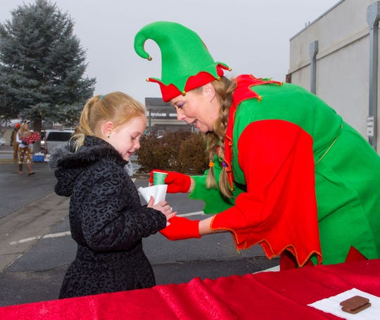 Deputy Clerk and Elf Leslie Dew-Hedrick hands out cookies and juice to Yerington Elementary School students during their visit with Santa at City Hall.