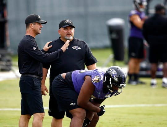 Baltimore Ravens head coach John Harbaugh, left, speaks with then-senior offensive assistant/tight ends coach Greg Roman as offensive tackle Ronnie Stanley prepares to run a drill during an NFL football training camp practice in Owings Mills, Md. Roman is off to a running start in his new role as offensive coordinator of the Baltimore Ravens, working on a ground game that maximizes the skills of quarterback Lamar Jackson.